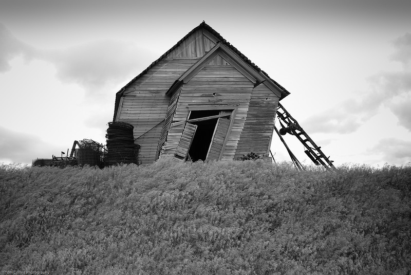 Leaning barn, held up by farm implement.