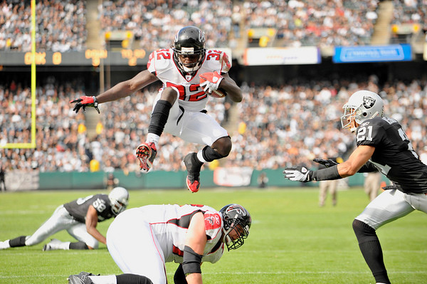 Nov. 2, 2008; Oakland, CA, USA; Atlanta Falcons running back Jerious Norwood (32) leaps past Oakland Raiders cornerback Nnamdi Asomugha (21) into the end zone for a first quarter touchdown during the Falcons game against the Raiders at Oakland-Alameda County Coliseum in Oakland, CA. Mandatory Credit: Daniel R. Harris-US PRESSWIRE