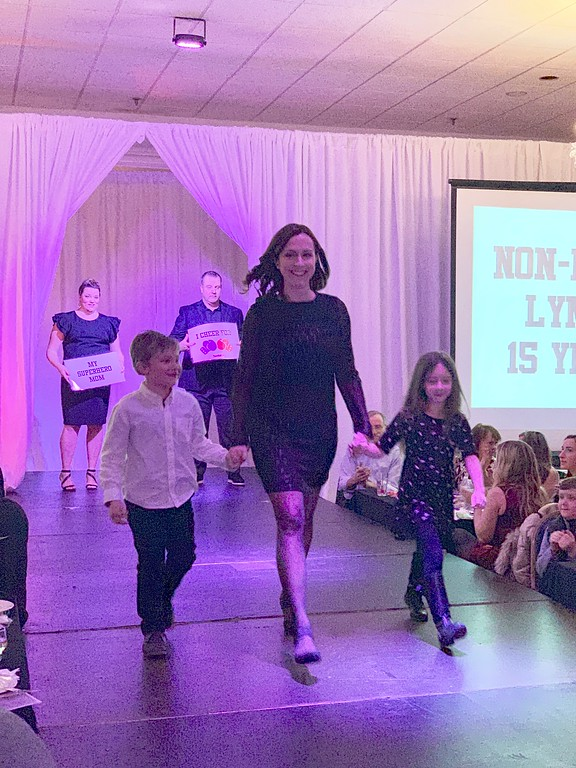 . Cancer survivor Laura Melancon of Westford struts her stuff with Ethan and Allison.