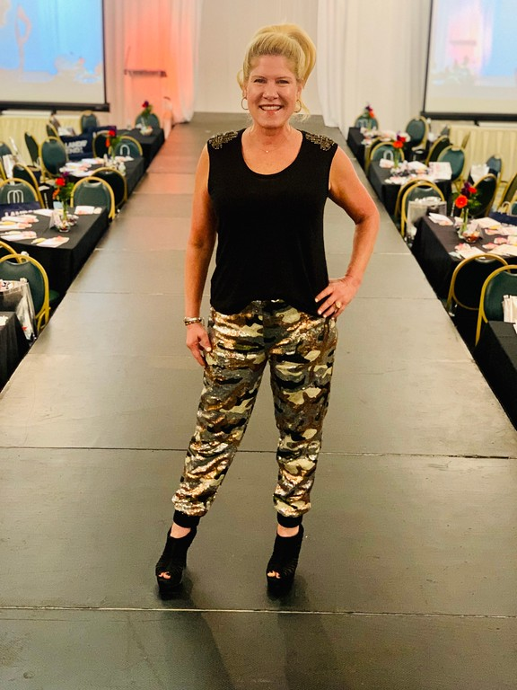 . Never fatigued for fashion: I�m wearing a pair of bronze, silver and green military fatigues made of all sequins! This look was fun � thank functional and trendy! I dressed it down with a Jennifer Lopez T-shirt with embedded rhinestones on the shoulders and a basic black open-toe ankle boot! My hair was swept up high in a classic ponytail, thanks to my hairdresser, Allison Bartolini of Cut to the Chase in Chelmsford, who also snapped this cute pic on the CatWalk!