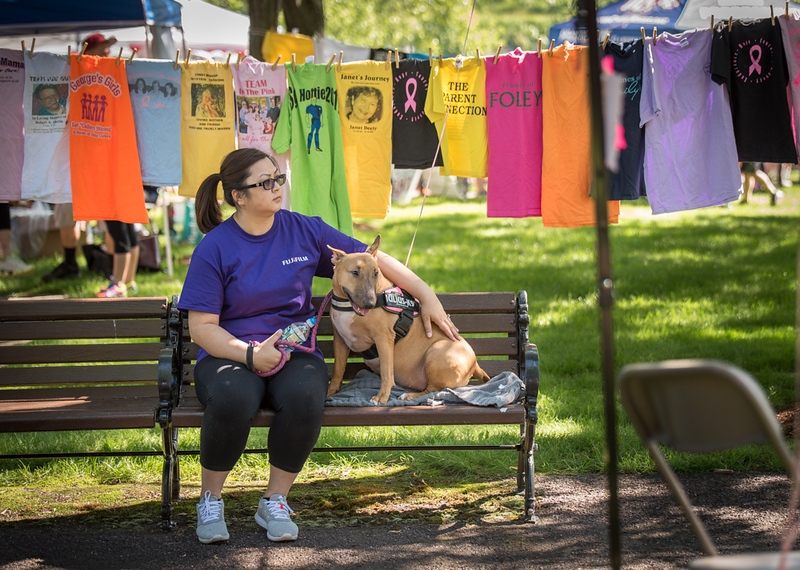 . Resting in front of the clothesline of remembrance for those who have passed, Sohia Chhim of Chelmsford, with her bull terrier, Remy.  The two are walking for Dexter, a fellow bull terrier from Falmouth, MA who passed away from spinal cancer.   The two were part of the 19th Annual Lowell General Hospital Teamwalk for CancerCare hosted on the grounds near the Tsongas Center in Lowell Sunday.   SUN/Scot Langdon