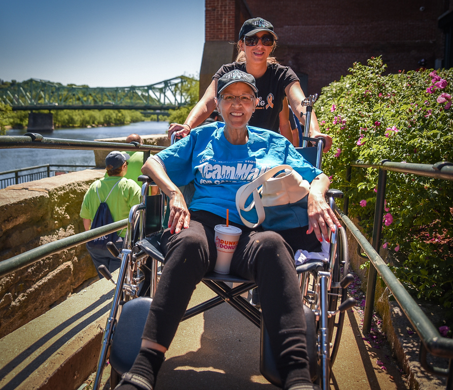 """. Deb Letendre, seated, of Dracut and Hollie Elwood, also of Dracut, part of Team Letendre, make their way around the course for the TeamWalk for CancerCare along the Merrimack River on Sunday.  Letendre says of the disease, \""""never give up\"""". The walk was part of the 19th Annual Lowell General Hospital Teamwalk for CancerCare hosted on the grounds near the Tsongas Center in Lowell Sunday.   SUN/Scot Langdon"""
