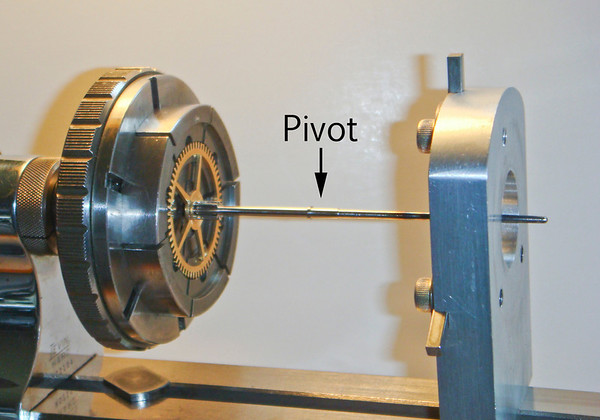 Figure 2 – Lathe set-up to Work the Pivot on a Vienna Regulator Minute Arbor Using Chuck 7 from Figure 3<br /> <br /> As you can see the gear is held in the jaws of the 6-jaw chuck, with the jaws of the chuck pressing against the teeth of the gear.  The benefit of 6-jaw chucks is that they have more jaws than a 3-jaw chuck; therefore they spread the strain over more of the teeth on the gear when set up this way.<br /> <br /> Note too that I use a steady when chucking up a gear with a 6-jaw chuck to minimize the strain on the gear hub.  Many times the gear is only pressed onto the arbor/pinion – resulting in a connection that is not strong enough to allow one to work a pivot when just holding the gear in a 6-jaw chuck.<br /> <br /> 6-jaw chucks come in a rather wide variety of designs – I have shown some of the more readily found ones in Figure 3.