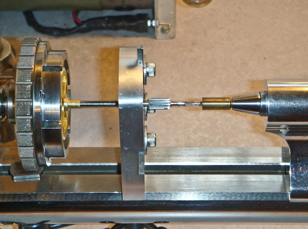 The end of the minute arbor is centered by a wax chuck that has had a cone cut into its end.  This aligns the gear in the chuck and the arbor in the steady.