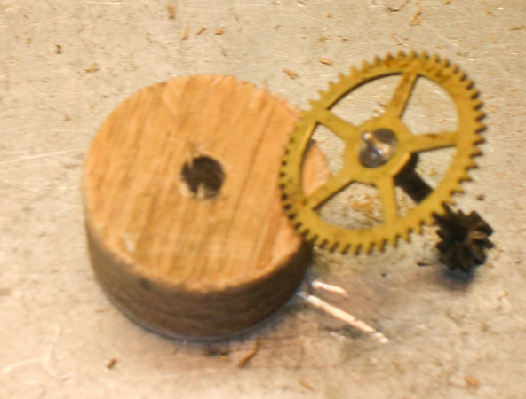 "Wooden disc cut out with a hole saw, and the gear that will be held by the ""no-jaw chuck"""