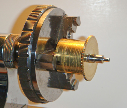 Figure 6 – Winding drum held in a 3 jaw chuck.  <br /> <br /> Once again, note the pivot on end of the arbor in Figure 6 – and its black surface.<br /> <br /> The jaws in the 3-jaw chuck in Figure 6 are somewhat similar to the jaws in the 6-jaw chuck shown in Figure 5 – in that they are stepped – allowing the jaws to hold a variety of sized drums.  Figure 6 shows one of the two orientations for the jaws in this particular chuck.  If the drum is small enough the jaws can be reversed and held very securely by the longer faces on the opposite end.  <br /> <br /> Both 3 and 6 jaw chucks often have solid arbors which preclude passing an gear arbors through them.  I drill the chucks arbors when I get the chucks to allow smaller arbors to pass through.  Take care to not drill so large a hole that you weaken the arbor.  I typically drill an 0.180 inch hole all the way through 8 mm arbors and have had no problems over the years with the arbors breaking.<br /> <br /> When working on larger winding drums I use my Myford lathe, with its larger accessory chucks.