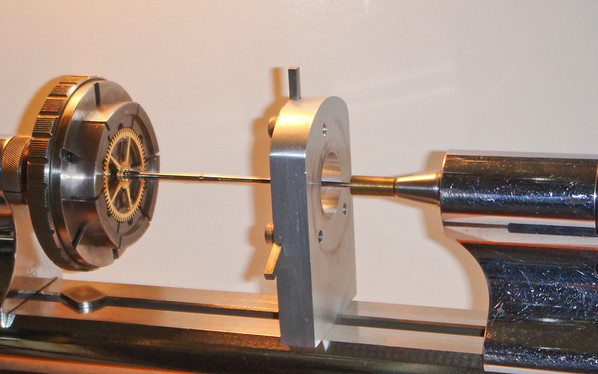 Figure 8 – Setting up to work the pivot on a minute arbor<br /> <br /> I first loosely grip the gear in the 6-jaw chuck and bring the tailstock forward such that the cone in the tailstock centers the gear.  Figures 9 and 10 show the tailstock cone in greater detail.  Those familiar with wax chucks will recognize that I used a wax chuck to make the tailstock cone.  A piece of brass rod is equally effective, either held in a collet in the tailstock, or shaped to match the taper in the tailstock runner.