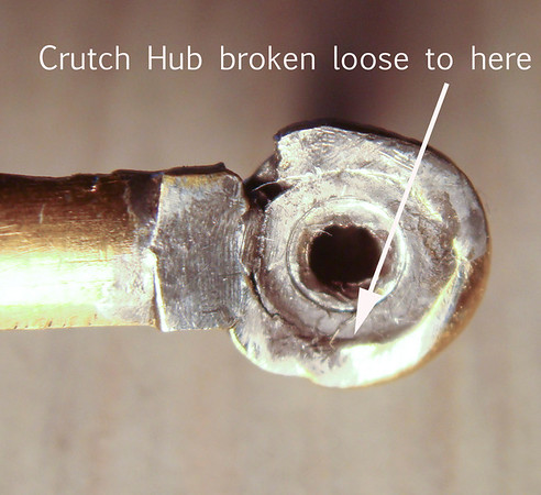 "Figure 1 – Crutch Hub ""as found""<br /> <br /> As can be seen, the crutch arm is meant to have a round hole which fits onto the brass hub that mounts on the anchor arbor.  This particular mechanism had led a hard life:  I suspect the hub was not original to the crutch arm, and someone had made a new arbor, which did not fit well.  The resultant connection between the hub and the arm was flexible enough that it contributed to keeping the mechanism from running.  That and someone had filed the pallets, shifted the pivot point for the anchor arbor, bent several pivots…  Well, let's just say there were lots of reasons it couldn't run.<br /> <br /> The first step was to remove the previously applied solder.  Heating the hub with a small butane torch allowed the two pieces to be separated – inserting a tooth pick into the hub as soon as the flame was withdrawn made it easier to remove the hub from the arm.  <br /> <br /> Lightly reheating the end of the separated crutch arm made it possible to wipe the excess solder away with a piece of cloth.  As mentioned in the safety section, wear a leather glove when wiping away excess solder with a piece of cloth to keep from getting burnt.<br /> <br /> An Exacto knife was then used to trim off residual solder that did not come off with the cloth.  Small files or sandpaper can also be used to remove residual solder.<br /> <br /> As shown in Figure 1, the original repairer did not do a good job of fitting the hole in the end of the arm to the hub.  It was possible to gently bend the rim of the hole such that the end of the rim touched the point where it was broken from the arm.<br /> <br /> Chucking up the hub in a jewelers lathe allowed me to cut off the excess solder and adjust the hub's diameter so that it fit the hole in the end of the arm.  Figure 2 shows the final fitment.  Please note – the pictures in this article are nearly all shot through a 10 power microscope – the outside diameter of the ring on the end of the crutch is just 5 mm, or less than a quarter of an inch.  The imperfections you see are truly very fine."