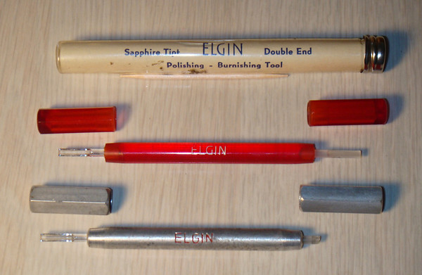 """Figure 2 – Elgin Sapphire Burnishers<br /> <br /> The bottom burnisher in Figure 2 has had a part of the pivot file (on the right hand end) broken off – both the Elgins and the commercial burnishers in Figure 1 have files at one of the burnisher.  I find both the files on the steel burnishers and the aluminum oxide slip (pivot file) on the Elgin burnisher to be very coarse, only appropriate for the initial flattening of a very badly damaged pivot.  Most of my pivot restoration work involves the use of hard Arkansas slips – as discussed in my first Tid-Bit (NAWCC Bulletin – """"Got Stones"""", October, 2009).<br /> <br /> Whilst too small for most clock work, the Elgin sapphire burnishers are perfect for watch work, and very appropriate for the smallest pivots in very fine clock mechanisms.<br /> <br /> Ray Ashcraft, a retired railroad watch inspector, used burnishers to restore both clock and watch pivots.  Fortunately he was not one to just accept the tools handed to him – he spent most of his career trying to make the best burnisher possible.  Each time I pick up the burnisher he passed on to me I am reminded of his efforts – not to mention when I open my burnisher drawer and see perhaps 15 other examples that were not quite as good.  With a lead-up like this you are probably beginning to think that making a burnisher is quite daunting, and well beyond the capabilities of a novice clock or watch restorer.  Hopefully this article will disabuse you of that notion.<br /> <br /> Size Matters<br /> <br /> Not to long ago I was reading an excellent article on moving pivots when assembling a mechanism (Some Thoughts on Pivot Locator Hooks - Bulletin Article 4/2010, pg 186).  The author presented a number of examples of hooks and pushers that can be used to move pivots around when trying to get them to slip into their appropriate holes.  I bring this up because I think it is an excellent lead-in for discussing why size matters in things like burnishers.  <br /> <br /> An experi"""
