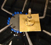 Tid-Bit 2 - Using a wax chuck : Published in the 12/2009 NAWCC Bulletin, page 695 Shellac Chucks – The perfect way to hold unusual bits and bobs in the Watchmakers Lathe This Tid Bit discusses how I cut out a disc of brass for the top of a clock weight. Sounds easy enough – eh, but, how to do it? Let's see – I guess I could use a jewelers saw to cut out a disc, drill it in the center, mount the rough disc on a mandrel, and then spin it in the lathe to clean up the edges and cut it to exact size. For those of you who have ever used a jeweler's saw, you know it is very satisfying; if indeed, rather slow work. OK. Show of hands – how many of you have ever used a shellac chuck (sometimes called a wax chuck)? Right, put your hands down – looked like around ten percent have used one. While I had never tried holding a flat piece of brass on a shellac chuck, it turned out to be a slick solution to my challenge. But to digress a bit. Shellac (or wax) chucks are typically used to hold very small parts that just can't be readily held any other way. For instance, the escape wheel from a watch. By gently heating the shellac chuck while it is mounted in a lathe, and then applying a bit of shellac or wax to the face of the chuck, and continuing to gently heat with the flame from an alcohol lam you can soften the shellac, mount, and then center the work piece on the chuck. The centering part is done while the lathe is spinning and the shellac is just softened (judicious application of the alcohol flame to the brass arbor between the shellac chuck and the collet). Believe it or not, it is possible, just using your finger, to center a gear on a shellac chuck so perfectly that you can repivot a very small arbor, like the escape wheel of a wrist watch. But, that is not what I did in this instance. This time I was holding a 2.5 inch square of 0.023 inch thick brass so I could cut out a circle. But, before we get to the technical part, let's spend a moment discussing safety. As you can see in the accompanying photos, we will be talking about doing a number of things that could hurt us. We will use heat to melt shellac, we will be spinning a square of metal in a jewelers lathe, and we will be generating fine metal shavings when we use the graver to true up the edges of the disc. While each of us has probably done such things a number of times before – it pays to take a minute and think through what could go wrong and what we should do to keep it from going wrong. Heat – each time you light the alcohol lamp, or the stove, think about what will be getting hot, and where the flame is. Especially with alcohol lamps, it is all too easy to not notice the virtually invisible flame – until you put your sleeve or arm into it. So, make a conscious effort to know where the flame is at all times. And, it also makes sense to extinguish the lamp when you get the work piece located on the chuck. Fortunately, the way I show mounting the brass to the plate keeps your fingers away from the flame, and from the heated brass sheet. Even when you pick up the collet to lift the plate off of the stove and place it on a towel, the collet will still be cool. None the less, wear safety glasses when working with the flame and the shellac. While it is unlikely that the shellac could pop or splatter, a little water in the shellac could cause steam and splattering. As shown in the pictures, I spun the square of brass plate on the lathe. This means there are sharp points spinning around which could readily cut you. As with the flame, you need to focus on where the risk is located, and consciously keep your hand, arm, and clothing away from it. If it makes you nervous, take a pair of tin snips and cut off the sharp corners, being careful to keep the deformation from the tin snip cuts away from the edge of what will be the finished disk. When you start cutting you will be generating fine shavings of brass. Be sure to be wearing safety glasses when cutting out the disc. Also take extra care when finishing the cut and parting off the square with the hole cut in the center. I found the actual separation point to be anticlimactic, but I was taking care to be extra observant and cautious as I approached that final cut.