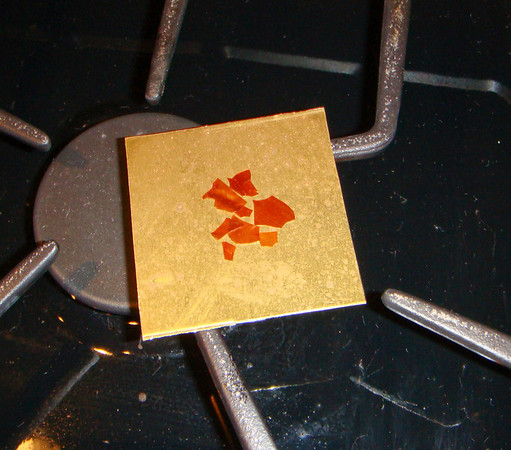 Figure 1 – Brass square ready to be heated.<br /> <br />  As you can see in the accompanying pictures, the first thing I did was melt some shellac flakes in the center of the brass square.  I did this on my gas range.  You can also do this readily on an electric range, with the heat turned down low.  In as much as shellac softens around 150 to 160 degrees F, we are not talking a lot of heat.<br /> <br /> A ready supply of shellac flakes can be found at most woodworking stores.  This is the same shellac that can be dissolved in alcohol and used as a wood finish.