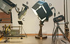 """Figure 8 – Typical Setup for Video-Recording Lathe Work<br /> <br /> It is not uncommon for me to try 6 or 8 light/camera location combinations before I get the lighting I want. <br /> <br /> The first time I video-recorded work on a lathe I realized that I would want to show both what my hands were doing, and what the lathe tool was doing.  This translated to a camera mounted on a microscope for the fine detail (labeled """"B"""" in Figure 8) and a second camera for recording what my hands were doing (labeled """"A"""" in Figure 8).  After viewing the recordings I realized that a third camera showing my hands from a different perspective (labeled """"C"""" in Figure 8) would be a good idea for those times my fingers got in the way of Camera A.<br /> <br /> One of the nice things about these cameras is that they each provide audio recording as well as video.  Which means that one can also choose which audio recording comes out best – in this case, likely A since it is farthest away from the lathe motor.<br /> <br /> With multiple videos it is possible to use a video-editing program to combine the specific bits of each recording that best tell the story you are tying to communicate.<br /> <br /> Lighting:  Simply put, you need lots of light.  I have used ordinary incandescent light bulbs and photo-floods, halogens, neon lights, and LED lighting.  While they all work, they also all have specific attributes that impact their effectiveness.<br /> <br /> Incandescent and halogen lights are good at providing a focused light.  Or, if used in conjunction with a light umbrella or a reflector they can provide an even, diffuse light.  They also get hot – floods and halogens especially can get warm enough that you might need a fan to keep yourself cool.<br /> <br /> Neon lights, in general, tend to make pictures come out a bit green, which is easy enough to remedy with photo-correction software.  The bulbs in my desk lamp, which are roughly 18 inches long, provide a nice, diffuse light, but they"""
