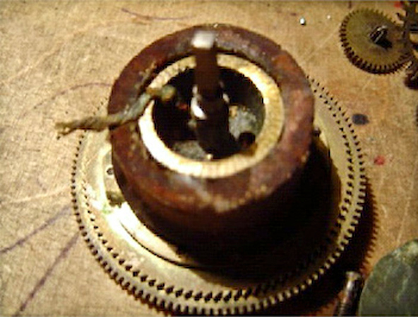 "Figure 1 - A wooden donut that Scottie found in a German Vienna-Style Regulator<br /> <br /> While Scottie's is perhaps the most ""inventive"", I have also come across winding drums that have been wrapped in tape, old news print, and thread.  All apparently in an attempt to increase the diameter of the drum, thereby getting a balky mechanism to run."