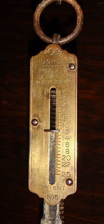 Figure 11 - This shot shows the scale with a retored mechanism and  the winding drum donut removed, and no nut on the crutch pin.  The minimum weight was 11.75 pounds (read on scale) plus 0.2 pounds for the weight of the scale, for a total of 12 pounds.<br /> <br /> When I removed the donut, and cleaned up the original drum, the mechanism continued to run until only 11.95 pounds remained.  With a 16 pound weight, this is a great margin for all the little challenges that can keep a mechanism from running (being out of beat, crutch pin too tight in the pendulum slot, pendulum wobble, case movement…).  And, with the donut removed, the mechanism runs for 16 months.<br /> <br /> But, the 11.95 pound weight was with no pendulum.  There was no question in my mind that a little inertia on the crutch would make the mechanism run longer/better.  But, I had never tested this hypothesis.  So, I put a 6 gram brass nut on the crutch pin and ran the experiment again.  This time the minimum weight was 10.95 pounds.