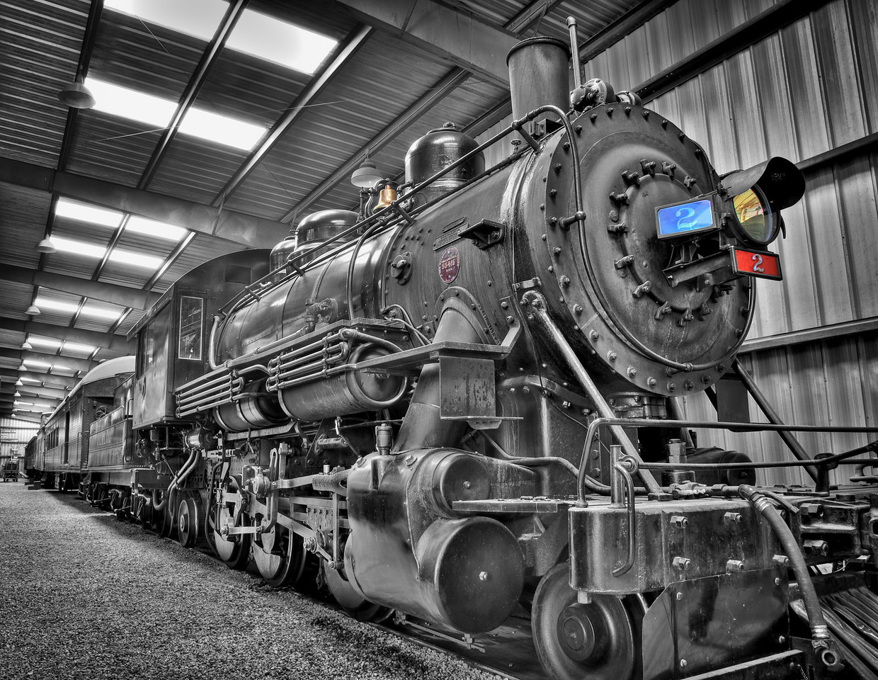 "4.  Massive. Powerful. Alive. A triumph of early 20th-century engineering, ready to roll. The visual image now matches my mental image, which I hope will be shared by other viewers. (In fact, this engine is maintained in operational condition.)<br /> <br /> More Photoshop work: first a mask in the black-and-white layer to let a few significant spots of color come through and pull your eye into the picture. Then more correction layers to punch-up the color spots, selectively bring back contrast in the most important parts of the image, and apply creative sharpening. The final print is made on Canson Baryta Photographique (luster surface) with photo black ink for deepest blacks and brightest whites. Bigger is better; 21""x27"" looked good for the show, but I could envision more, maybe even on aluminum!"