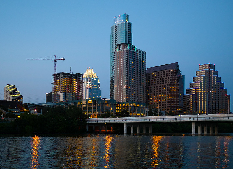 Austin late evening skyline from the Butler Hike and Bike Trail by Ted Lee Eubanks. The bridge seen in the image is the 1st Street Bridge, constructed in 1951.