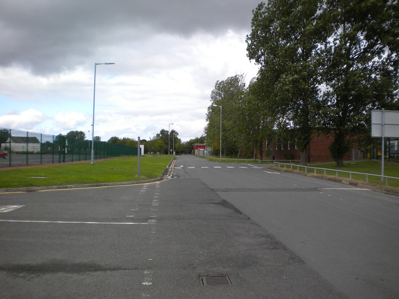 This picture shows the main service road that leads out onto the <br /> <br /> main road the A67 trailing away.<br /> <br /> The actual Main Airport Terminal building is to the Left where the <br /> <br /> road turns off in the picture and the Road to the Station is to the right <br /> <br /> of me of which more in a minute.<br /> <br /> When I came here for the first time in June 2007 I walked from the <br /> <br /> road out of sight to the right across the picture and went through <br /> <br /> what was an open road to the left and through to Catch the Arriva <br /> <br /> bus back to Middlesbrough which no longer runs this was also the <br /> <br /> easy way to get to the Shuttle bus that ran from Darlington Station <br /> <br /> which has also since ceased running <br /> <br /> And the road to the Left that I used when I came back in Oct 2007 <br /> <br /> with Liz now had a massive gate across it!!<br /> <br /> And so if it wasn't for the Bus showing up and a confused bus driver <br /> <br /> we would have had a very long walk back to the Terminal <br /> <br /> Because as you can see from the Map you now have to walk up the <br /> <br /> road in the picture to the Main A67 road then back in on yourself to <br /> <br /> get to the Terminal that don't include the walk you have already <br /> <br /> done from the station!!!