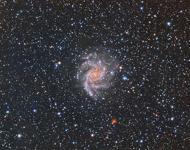 "NGC6946: Fireworks Galaxy. RGB. 0.96""/pixel image scale.  Astrodon Red filter,  10 x 10 minutes, 1x1. 8/15/2014.  Astrodon Green filter, 10 x 10 minutes, 1x1. 8/15/2014.   Astrodon Blue filter, 10 x 10 minutes, 1x1. 8/15/2014.    TEC 140 APO F/7 with Astro-Physics A-P1100GTO GEM. QSI660wsg. Guided with A-P Vario Finder 250mm focal length and Superstar, Optec Handy Stepper Motor focuser.   Captured and automated with SGP. Calibration (including Dark Subtraction) and Post-processed with PixInsight. PHD2 settings: RA Aggressiveness: 60, RA Hysteresis: 10, Max RA/Dec Duration: 1000, Min Motion: 0.10, Calibration Steps: 550msec, Auto/Resist Switching, Extreme dithering and Settle at < 0.4, 1 sec guiding exposure."