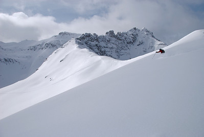 A skier drops out the gate of the Telluride Ski Resort on a deep powder day
