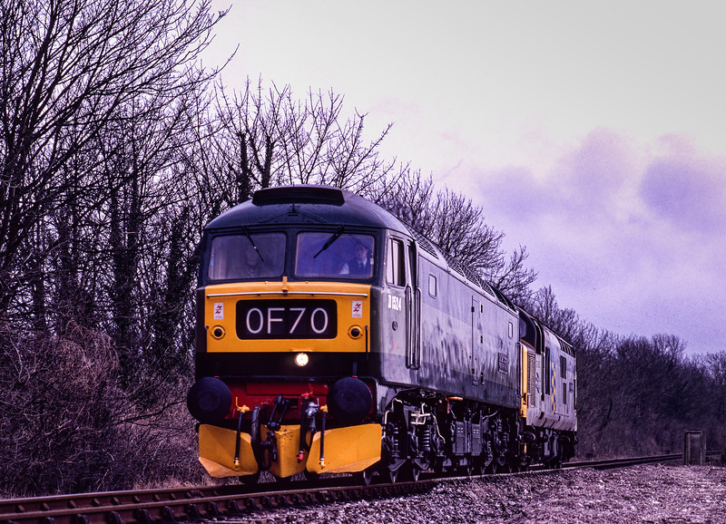 """47004 and 37892 working LD from Ropley to Alresford, on 5th March 1994. 47004 not only carried the """"Old Oak Common"""" nameplates, it also carried the 0F70 headcode. This was the usual headcode for any light engine move to Old Oak Common. Scanned Transparency."""