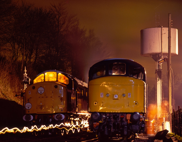"The night before the Gala, 40012 ""Aureol"" and 45132 at Ropley. The flurry of activity on the right of the 45 is due to last minute repairs to cure a water leak. I was part of the Peak support crew at the time, so I set my camera on the tripod and went back to work. This exposure was timed at 8 minutes. Scanned Transparency."