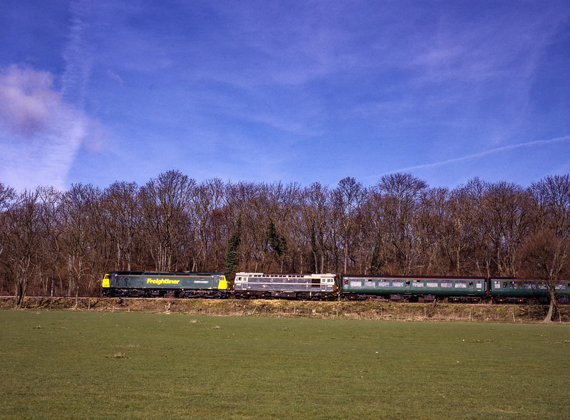 57011 and 33208 passing Baigents Copse with the 10:53 Alton - Alresford<br /> on 5th March 2000. Scanned Transparency.