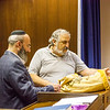 Synagogue leader Ken Wolf and Shmuel Bowman examine Torah Scroll