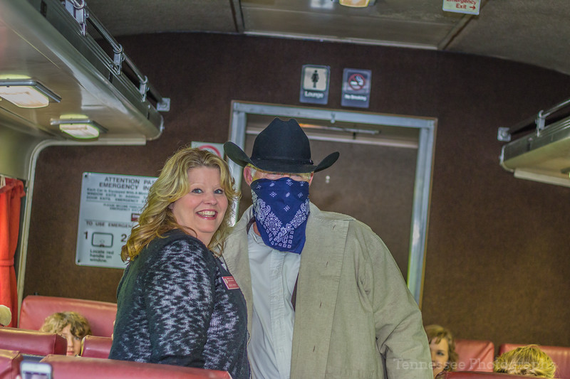 Car host Becky White is accousted by a train robber