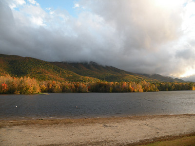 The far shore of the lake is lit by the evening sun