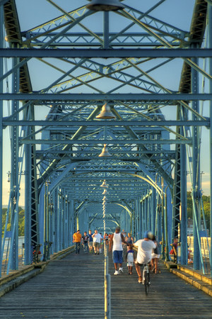 People enjoy a sunset walk across the Walnut Street Bridge in Chattanooga, TN on Wednesday, July 22, 2015. Copyright 2015 Jason Barnette