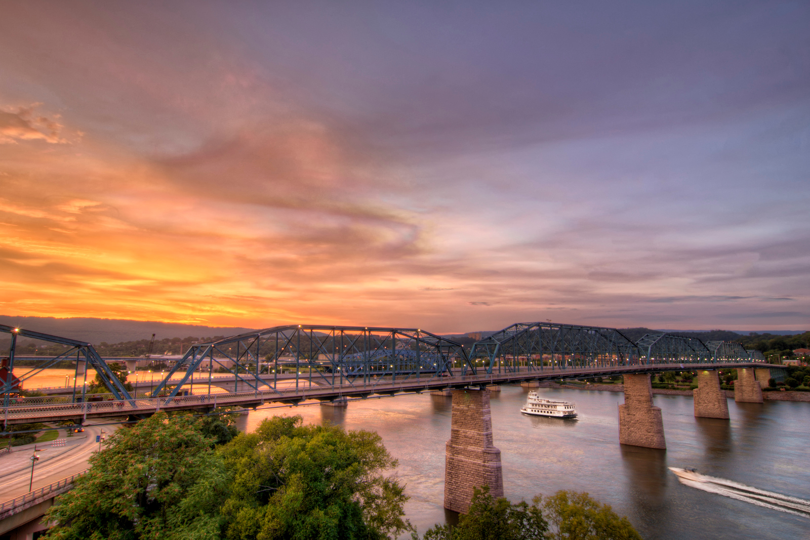 A warm sunset along the Tennessee River as the Southern Belle Riverboat and a private boat pass under the Walnut Street Bridge in Chattanooga, TN on Monday, July 20, 2015. Copyright 2015 Jason Barnette