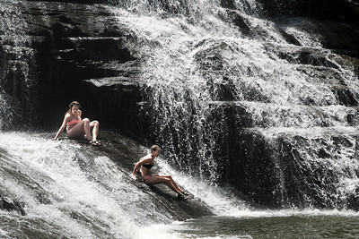 Two women slide down the slippery rocks of Cane Creek Cascades at Fall Creek Falls State Park in Spencer, TN on Thursday, July 16, 2015. Copyright 2015 Jason Barnette