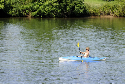 A woman paddles a kayak along the Tennessee River near Ijams Nature Center in Knoxville, TN on Saturday, June 7, 2014. Copyright 2014 Jason Barnette