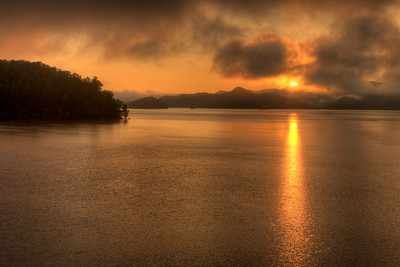 The rising sun peaks over the mountain ranges surrounding South Holston Lake in Bristol, TN on Friday, July 25, 2014. Copyright 2014 Jason Barnette