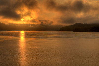 The sun rises and burns through heavy fog over South Holston Lake in Bristol, TN on Friday, July 25, 2014. Copyright 2014 Jason Barnette