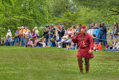 A Native American reenactor walks across the field in front of the spectators after the Siege of Fort Watauga at Sycamore Shoals State Park in Elizabethton, VA on Saturday, May 17, 2014. Copyright 2014 Jason Barnette  The Siege of Fort Watauga is a two-day reenactment held each year at the recreation of the fort inside Sycamore Shoals State Historic Park. The reenactment brings in dozens of reenactors and hundreds of visitors as they tell the story of an attack on the early settlers village by Dragging Canoe, and how they successfully defended themselves. During the reenactment, the fort is open to the public with demonstrations of all areas of early settler life on the frontiers.