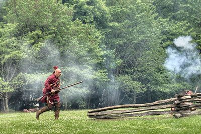 A Native American reenactor runs across an open field during the Siege of Fort Watauga at Sycamore Shoals State Park in Elizabethton, VA on Saturday, May 17, 2014. Copyright 2014 Jason Barnette  The Siege of Fort Watauga is a two-day reenactment held each year at the recreation of the fort inside Sycamore Shoals State Historic Park. The reenactment brings in dozens of reenactors and hundreds of visitors as they tell the story of an attack on the early settlers village by Dragging Canoe, and how they successfully defended themselves. During the reenactment, the fort is open to the public with demonstrations of all areas of early settler life on the frontiers.