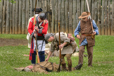 A British reenactor checks the pulse of a fallen settler during the Siege of Fort Watauga at Sycamore Shoals State Park in Elizabethton, VA on Saturday, May 17, 2014. Copyright 2014 Jason Barnette  The Siege of Fort Watauga is a two-day reenactment held each year at the recreation of the fort inside Sycamore Shoals State Historic Park. The reenactment brings in dozens of reenactors and hundreds of visitors as they tell the story of an attack on the early settlers village by Dragging Canoe, and how they successfully defended themselves. During the reenactment, the fort is open to the public with demonstrations of all areas of early settler life on the frontiers.