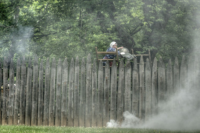 A woman, portraying Ann Robertson Johnson, throws water over the wall of the fort during the Siege of Fort Watauga at Sycamore Shoals State Park in Elizabethton, VA on Saturday, May 17, 2014. Copyright 2014 Jason Barnette  The Siege of Fort Watauga is a two-day reenactment held each year at the recreation of the fort inside Sycamore Shoals State Historic Park. The reenactment brings in dozens of reenactors and hundreds of visitors as they tell the story of an attack on the early settlers village by Dragging Canoe, and how they successfully defended themselves. During the reenactment, the fort is open to the public with demonstrations of all areas of early settler life on the frontiers.