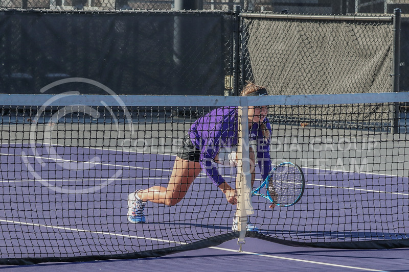 Crouching behind the net, junior Ioana Gheorghita anticipates a serve from her opponent. K-State hosted Iowa State and KU in their Fall Invitational on October 30 through November 1 at Mike Goss Tennis Stadium.<br /> (Macey Franko | Collegian Media Group)