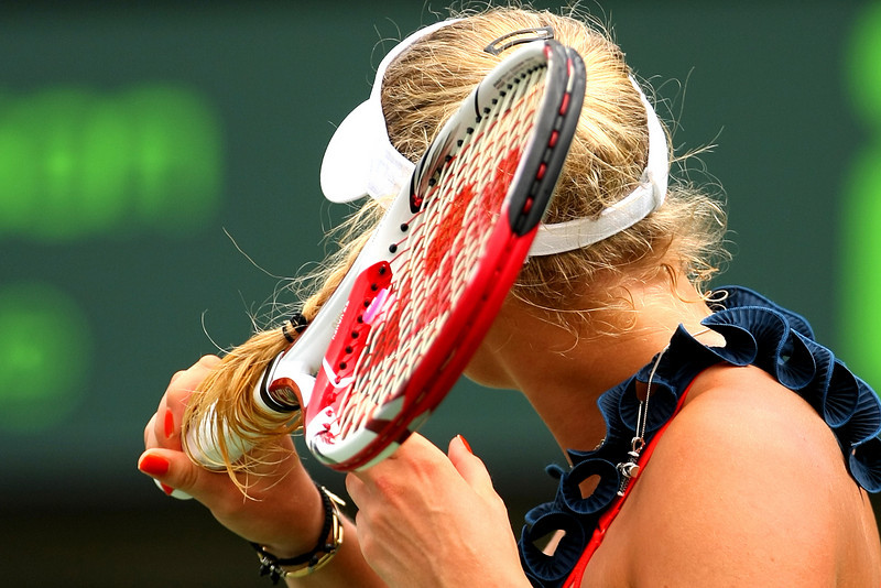Caroline Wozniacki of Denmark wraps her hair around her racquet in Miami