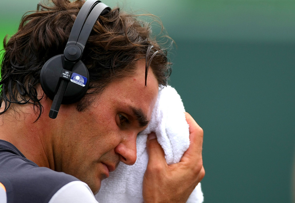 Roger Federer of Switzerland wipes his brow whilst wearing headphones in Miami