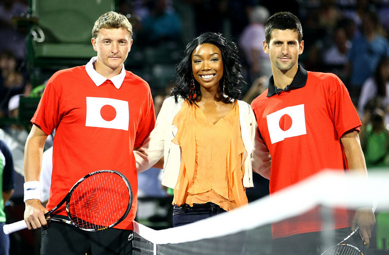 Novak Djokovic of Serbia and Denis Istomin pose with Brandy at the net to raise money for the Japan disaster in Miami