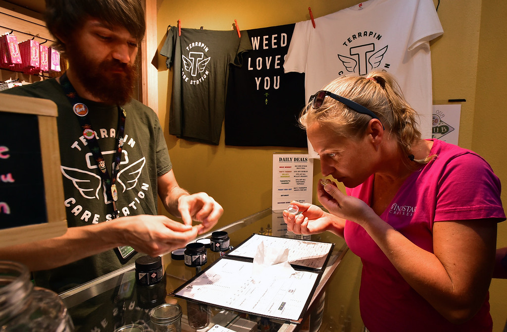 . Kristi Skaggs takes in the fragrance of a concentrate as she thinks about buying different products with Max DiGennaro, a supervisor at Terrapin Care Station in Boulder on Monday.  Paul Aiken Staff Photographer July 2, 2018