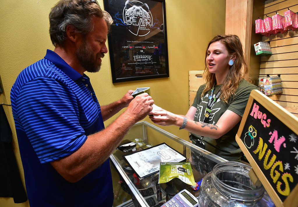 . David Hathaway checks out the fragrance of a cannabis product with Bud Tender Julia Greff at Terrapin Care Station in Boulder on Monday.  Paul Aiken Staff Photographer July 2, 2018