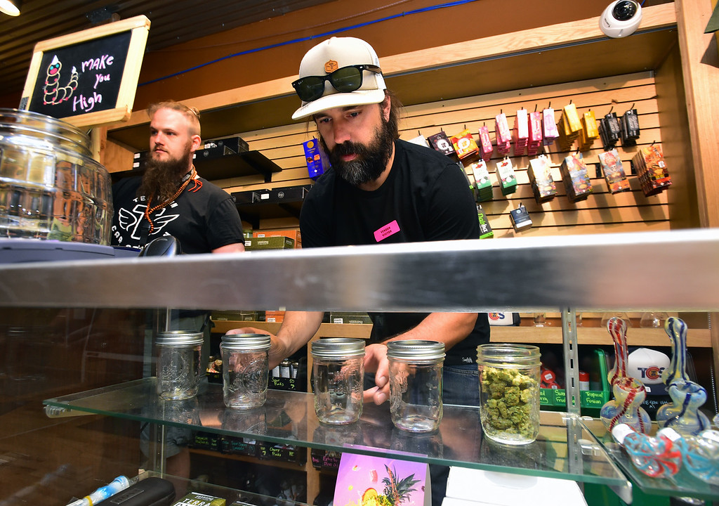 . James Kelley, a Store Manager at Terrapin Care Station, works on setting up a display case at their store in Boulder on Monday.  Paul Aiken Staff Photographer July 2, 2018