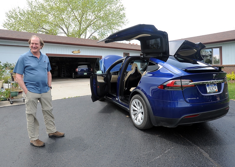 Bruce Robinson shows off his brand new Tesla X in the driveway of his Loveland home on Wednesday, May 11, 2016. He and his wife, Linda Robinson believe this is the first production model Tesla X in Colorado. (Photo by Jenny Sparks/Loveland Reporter-Herald)