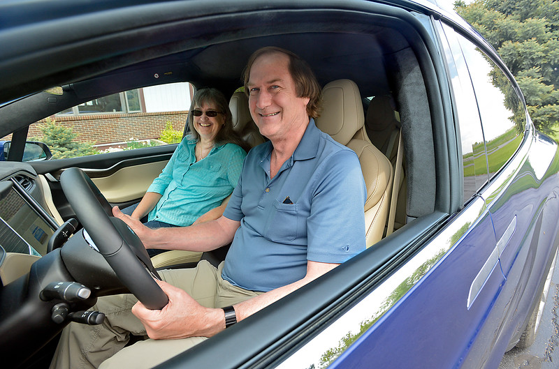 Bruce Robinson and his wife, Linda Robinson pose for a photo in their brand new Tesla X in the driveway of their Loveland home on Wednesday, May 11, 2016. They think this is the first production model Tesla X in Colorado. (Photo by Jenny Sparks/Loveland Reporter-Herald)