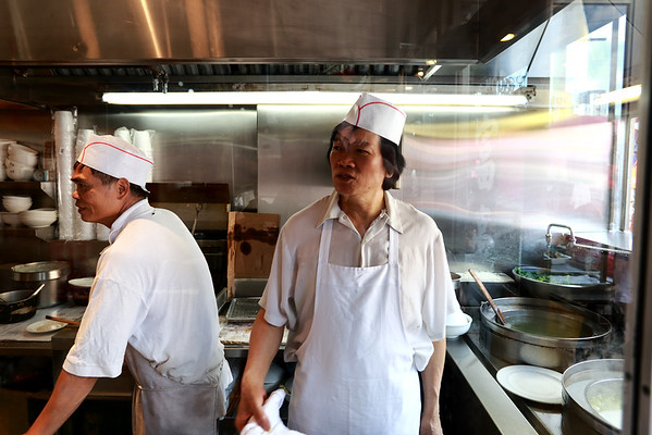 Cooks at King's Noodle in Toronto's Chinatown look on at the action in the restaurant