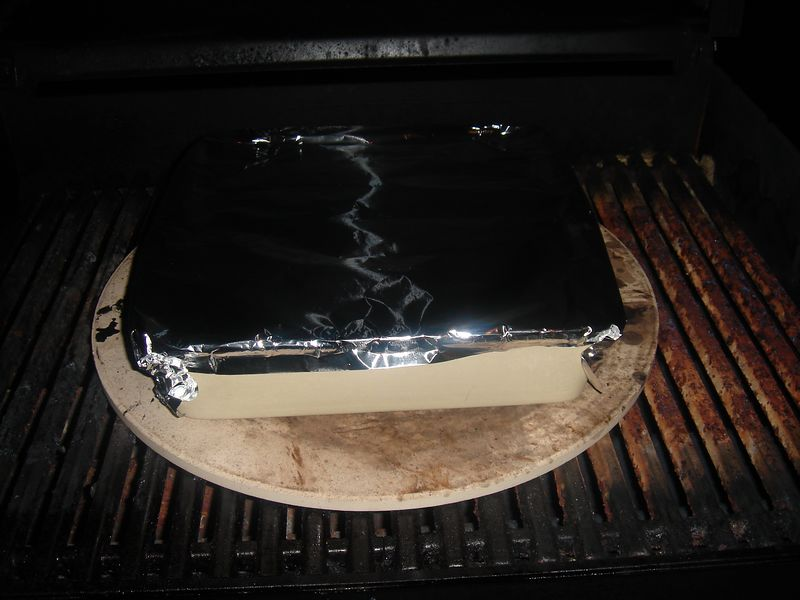 Cover with alumonim foil. Fire-up the grille using medium flame on a Webber propane grille. Close the grille cover and cook for about 40 minutes so that broth is fully bubbling around the corners and the fish has turned from  translucent to flakey-white.